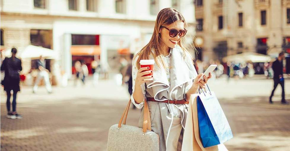Happy-woman-reading-smartphone-and-shopping
