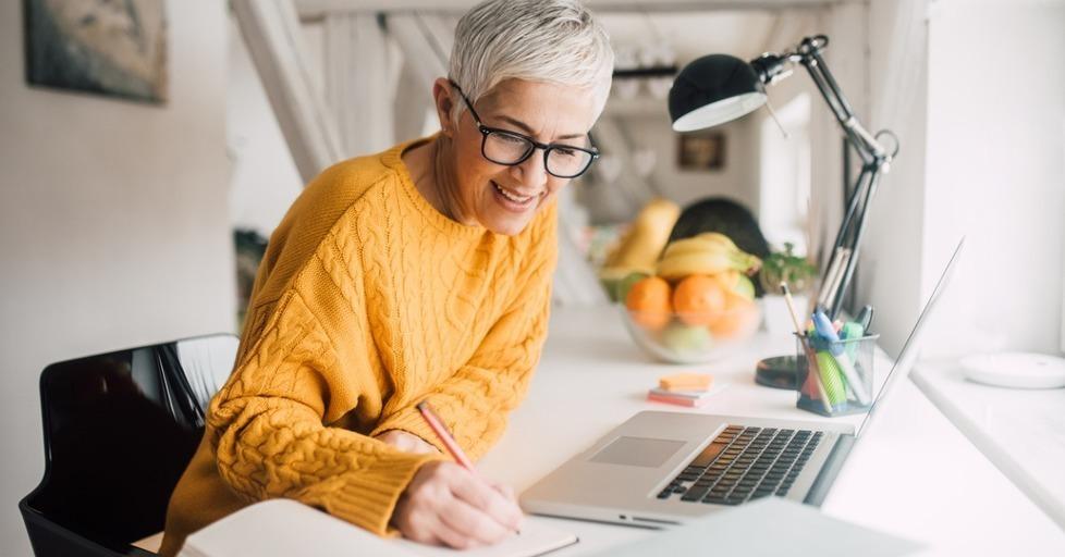 Older_woman_writing_at_desk